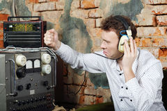 Man in headphones knocks on power source to radio receiver. Man in big white headphones knocks on power source to radio receiver in very old house Stock Images