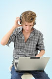Man with headphones and laptop Stock Images