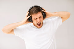 Man with headphones listening loud music. Young man with headphones listening loud music royalty free stock photography