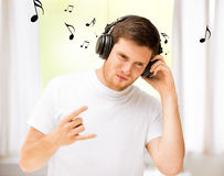Man with headphones listening rock music at home Stock Photos