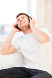 Man with headphones listening to music. Happy man with headphones listening to music at home Royalty Free Stock Image