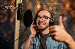 Man with headphones at music recording studio. Music, show business, people and voice concept - male singer with headphones and microphone singing song at sound Royalty Free Stock Image