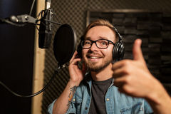 Man with headphones at music recording studio. Music, show business, people and voice concept - male singer with headphones and microphone singing song at sound Royalty Free Stock Images