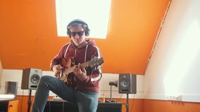 A man in headphones playing guitar in the bright sound recording studio. Mid shot