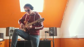 A man in headphones playing guitar in sound recording studio. Mid shot