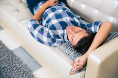 Man with headphones resting on the sofa at home Stock Image