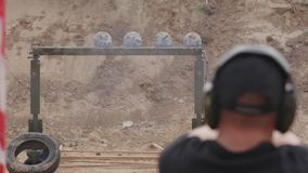 FullHD footage. Man in headphones shoots a pistol on the target plates. stock video