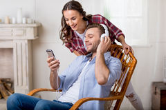 Man in headphones showing something on smartphone to cheerful woman behind. Smiling men in headphones showing something on smartphone to cheerful women behind Royalty Free Stock Images