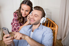 Man in headphones showing something on smartphone to cheerful woman behind. Smiling men in headphones showing something on smartphone to cheerful women behind Stock Image