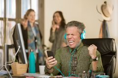 Man with Headphones Singing Loudly and Annoying Colleagues. Professional men singing loudly enough to annoy colleagues in background stock photo