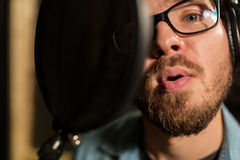 Man with headphones singing at recording studio Stock Images