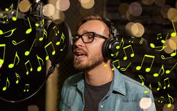 Man with headphones singing at recording studio. Music, show business, people and voice concept - male singer with headphones and microphone singing song at Royalty Free Stock Photo