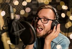 Man with headphones singing at recording studio. Music, show business, people and voice concept - male singer with headphones and microphone singing song at Royalty Free Stock Images