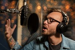 Man with headphones singing at recording studio. Music, show business, people and voice concept - male singer with headphones and microphone singing song at Royalty Free Stock Image