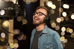 Man with headphones singing at recording studio. Music, show business, people and voice concept - male singer with headphones and microphone singing song at Stock Photography