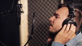 Man with headphones singing at recording studio stock video