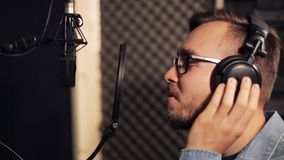 Man with headphones singing at recording studio stock video footage