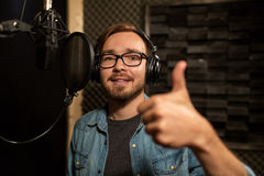 Man with headphones singing at recording studio. Music, show business, people and voice concept - male singer with headphones and microphone singing song at Stock Image
