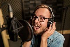 Man with headphones singing at recording studio Stock Photos