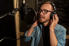 Man with headphones singing at recording studio Royalty Free Stock Image