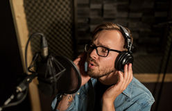 Man with headphones singing at recording studio Royalty Free Stock Images