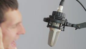 Man in headphones singing at studio microphone stock video footage