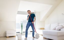 Man in headphones singing to by mop at home Royalty Free Stock Images