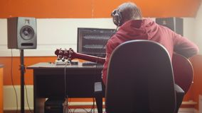 A man in headphones sitting by the computer in the studio and recording a song. Mid shot