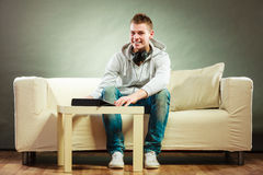 Man with headphones sitting on couch with tablet Royalty Free Stock Photo