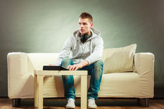 Man with headphones sitting on couch with tablet Stock Image