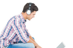 Man with headphones sitting on the floor using laptop Stock Photo