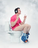 Man in headphones sitting on the toilet. Stock Images