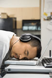 Man with headphones sleeping on laptop. Stock Image