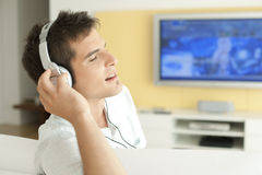Man with Headphones and TV. Young man listening to music with headphones at home Stock Photos