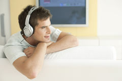 Man with Headphones and TV. Young man listening to music with headphones at home stock image