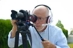 Man with headphones, using a camera dslr Royalty Free Stock Photo