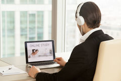 Man in headphones using online study course. Man in headphones at of laptop with online study service web page on screen. Office worker chooses free online stock photo