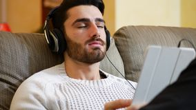 Man with headphones using tablet PC. Handsome young man in headphones sitting and using digital tablet PC at home stock video footage