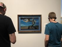 Man with headphones watching at the picture in museum stock photography