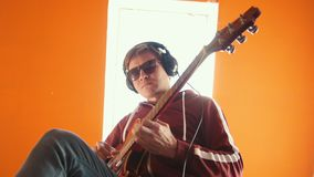 A man in headphones wearing glasses playing guitar in the studio. Mid shot