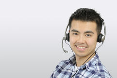 Man with headset. Head shot of a young Asian Man wearing a telephone headset Stock Image
