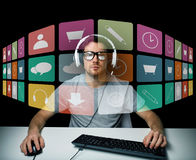 Man in headset with computer and icons on screen Royalty Free Stock Image