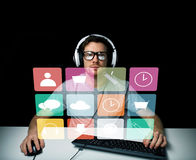 Man in headset with computer and icons on screen Stock Images