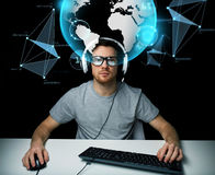 Man in headset with computer over earth projection. Technology, cyberspace, virtual reality and people concept - hacker man in headset and eyeglasses with pc Stock Photo
