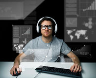 Man in headset with computer over virtual screens Stock Photography