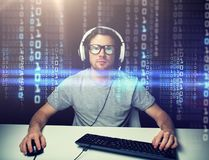 Man in headset hacking computer or programming. Technology, cyberspace, virtual reality and people concept - man or hacker in headset and eyeglasses with stock photos