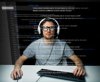 Man in headset hacking computer or programming Royalty Free Stock Image