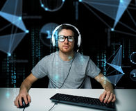 Man in headset hacking computer or programming Stock Photos