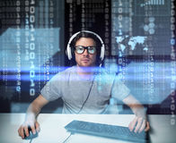 Man in headset hacking computer or programming. Technology, cyberspace, virtual reality and people concept - man or hacker in headset and eyeglasses with Royalty Free Stock Photo