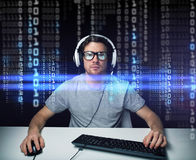 Man in headset hacking computer or programming Royalty Free Stock Images